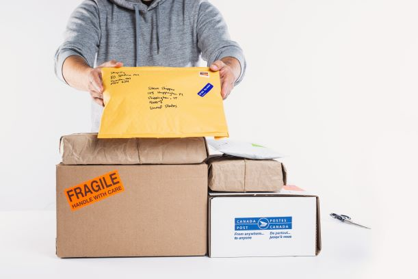 a-man-holding-up-packages-for-fulfillment sm